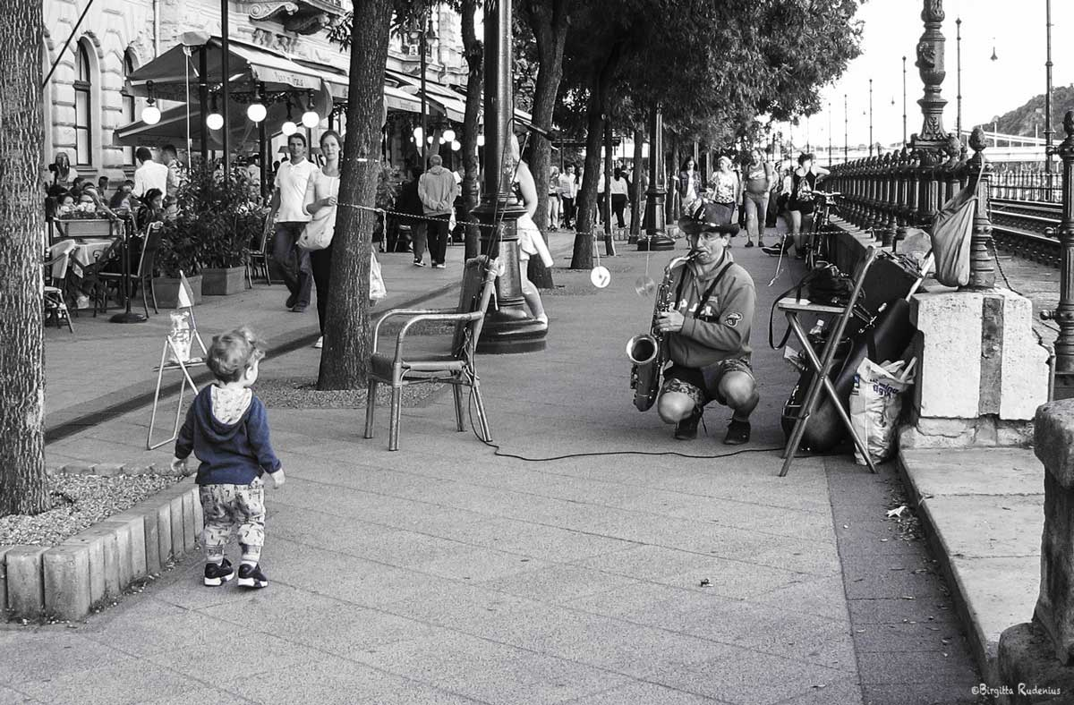 Street Photo - Julius the street musician plays for the little boy.